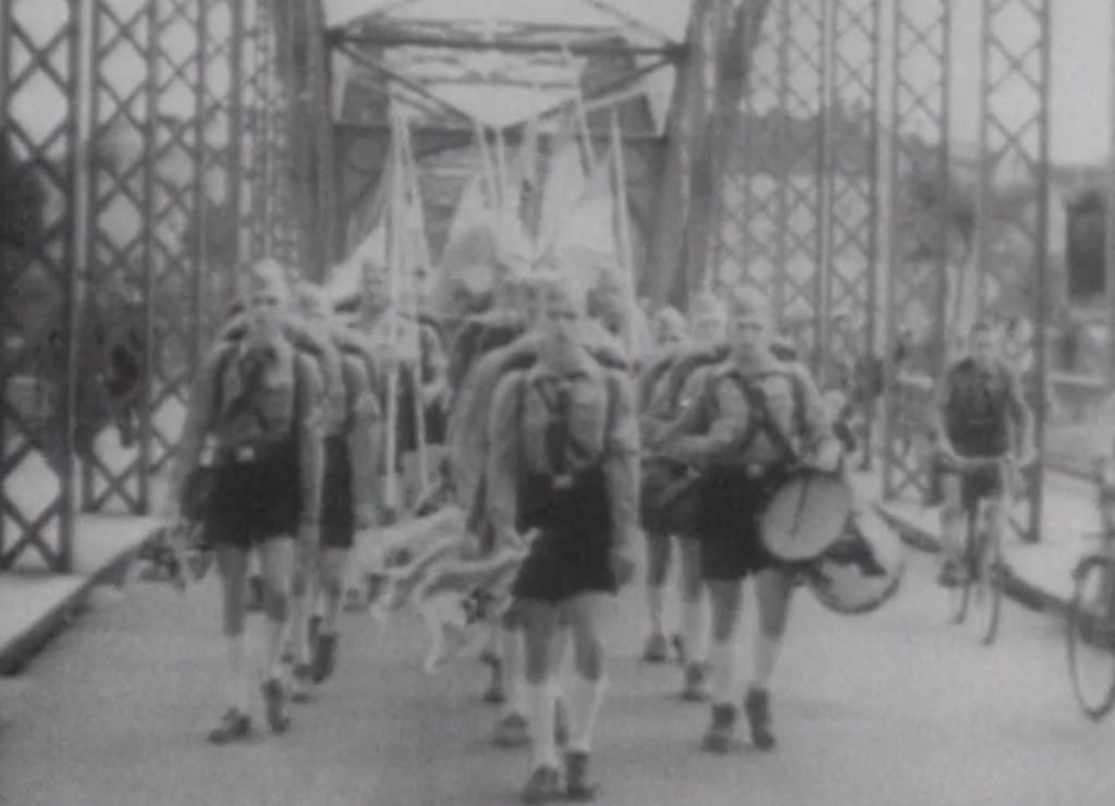 Jóvenes alemanes marchando, cargando banderas e instrumentos de banda de guerra.